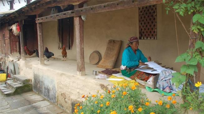 Gurung woman weaves on the porch